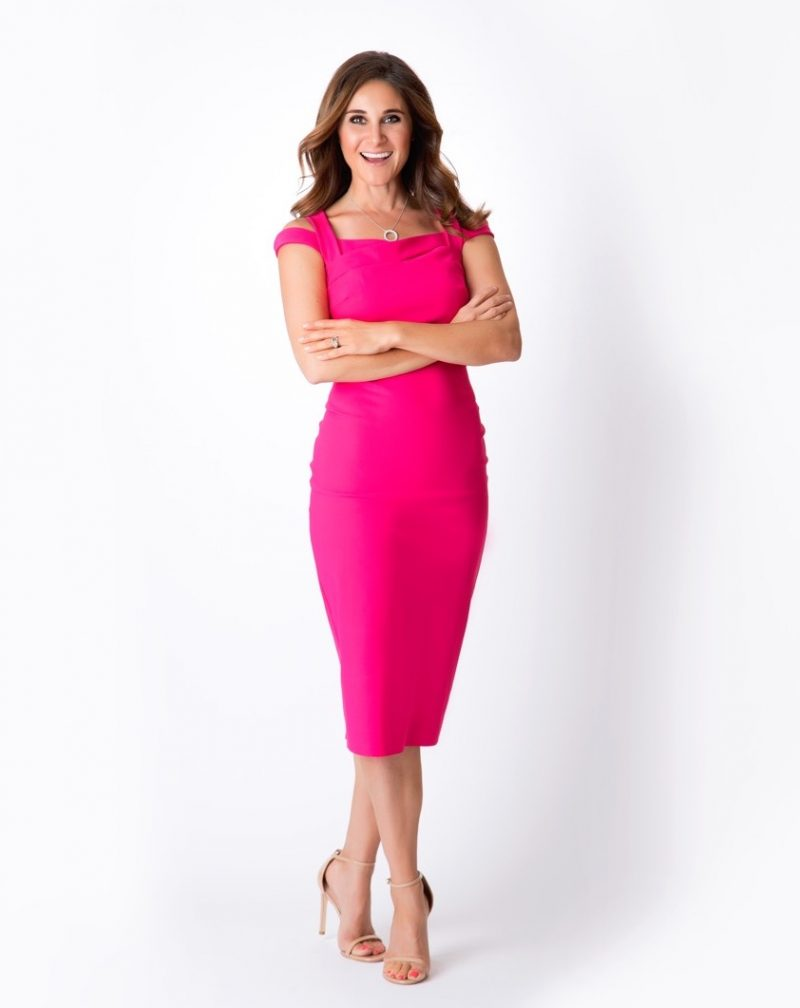 Rebecca Traverso wears a pink dress and crosses her arms as she smiles at the camera