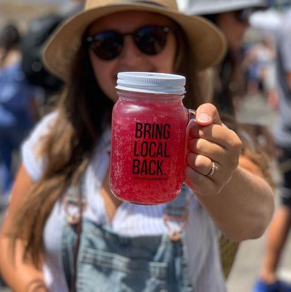 "a mason jar filled with bright pink kombucha reads ""bring local back"""