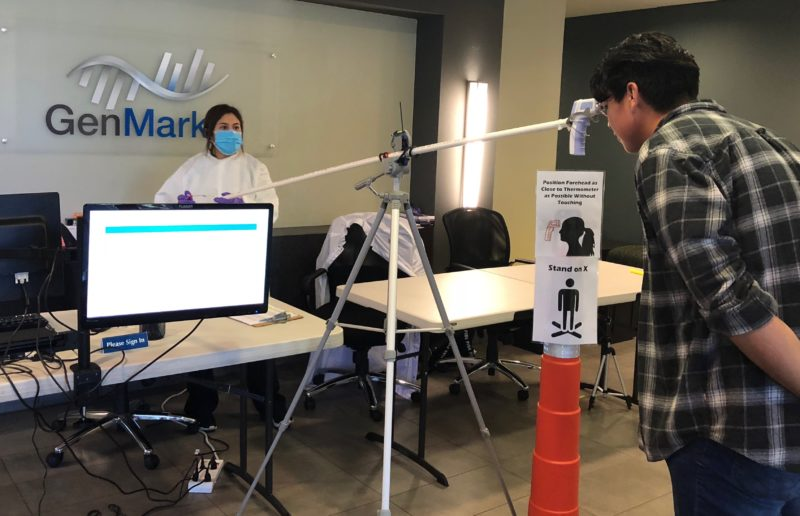 Two employees run an experiment inside GenMark's Carlsbad office